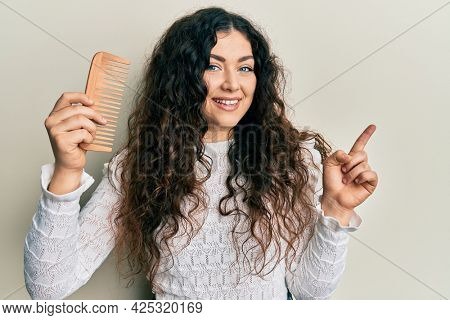 Young brunette woman with curly hair styling hair using comb smiling happy pointing with hand and finger to the side