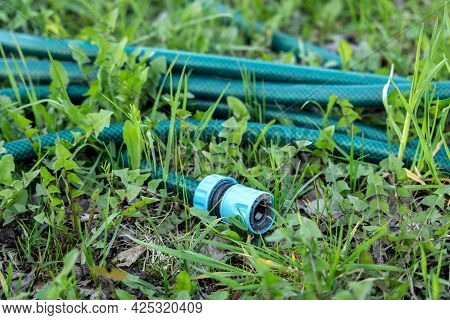 Green Garden Hose With Fixture Lying On The Grass. Close Up.