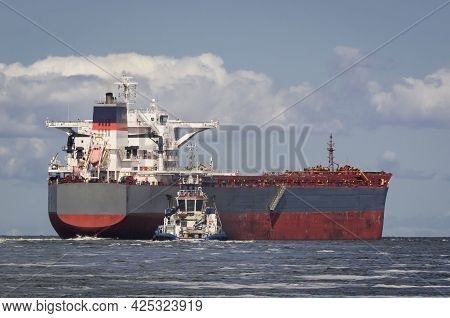 Bulk Carrier - The Ship Sails From Port To Sea Secured By Tug
