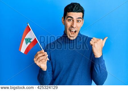 Handsome hispanic man holding lebanon flag pointing thumb up to the side smiling happy with open mouth
