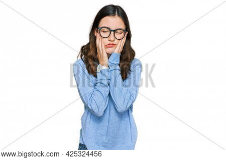 Young beautiful woman wearing casual clothes and glasses tired hands covering face, depression and sadness, upset and irritated for problem