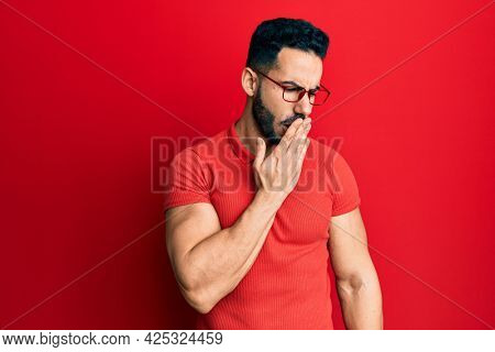 Young hispanic man wearing casual clothes and glasses bored yawning tired covering mouth with hand. restless and sleepiness.