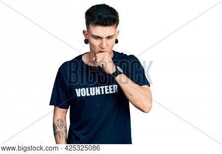 Young caucasian boy with ears dilation wearing volunteer t shirt feeling unwell and coughing as symptom for cold or bronchitis. health care concept.