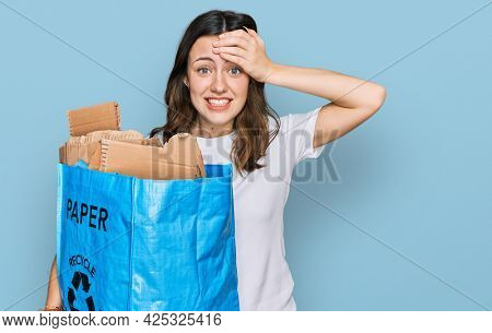 Young beautiful woman holding recycling wastebasket with paper and cardboard stressed and frustrated with hand on head, surprised and angry face