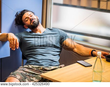 Bearded Muscular Man Sleeping At Cafe Table Or In Kitchen