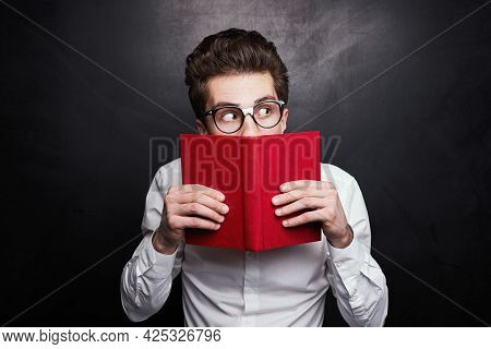 Clever Young Male Student In White Shirt And Nerdy Spectacles Hiding Behind Red Book And Looking Wit