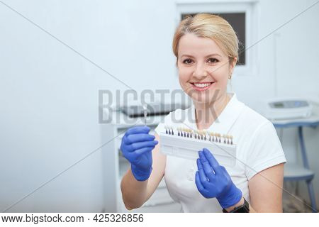 Charming Female Dentist Smiling To The Camera, Holding Teeth Whitening Shade Chart, Copy Space