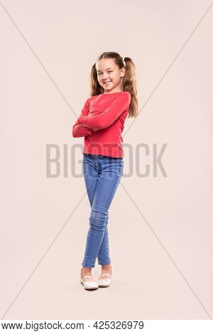 Full Body Of Positive Preteen Girl With Ponytails Dressed In Casual Red Sweatshirt And Jeans Standin