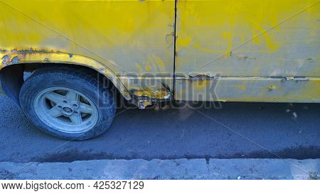 Old Dirty Yellow Car On Road. Sheet Metal Corrosion Over Auto Tyre Wheel. Rusty Messy Surface. Damag
