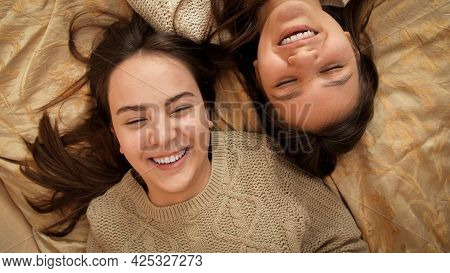 Camera Rotating Over Two Teenage Girls Lying On Bed And Talking. Teenager Friendship And Relationshi