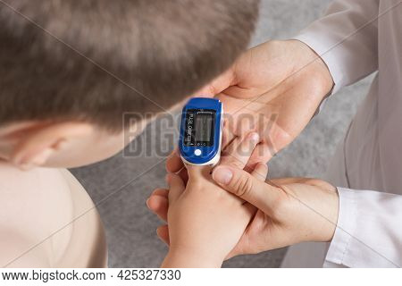 The Pediatrician Measures The Childs Blood Oxygen Level With A Pulse Oximeter. Pneumonia And Coronav