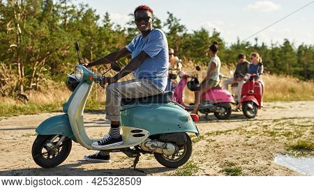 Cheerful Young African American Boy Resting On Retro Scooter Outdoors In Warm Sunny Day With Company