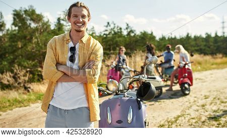 Cheerful Young Caucasian Boy Resting Beside Retro Scooter Outdoors In Warm Sunny Day With Company Of