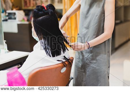 Woman Hairdresser With Scissors Starting To Cut Client Hair