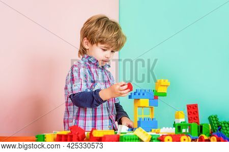 Educational Toys For Young Children. Little Boy Playing With Lots Of Colorful Plastic Blocks Constru