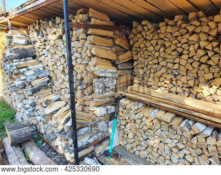 A Lot Of Firewood Stacked Evenly In The Yard For Winter. Wooden Birch Logs, Bonfire. Firewood Cleave
