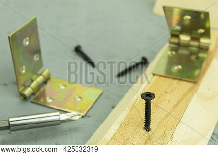A Black Screw Is Screwed Into The Board. Carpenter's Work Process, Self-tapping Screw Is Screwed Int