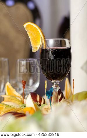 Glass Of Red Wine And A Slice Of Orange Fruit Snacks On The Banquet Table