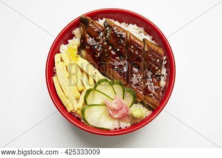 Bowl Of Rice Topped With Broiled Eel In Unagi Sauce On White Background.