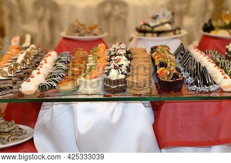 Catering A Lot Of Sweet Snacks From Small Cakes With Cream And Chocolate Cream And Fruit On The Glas