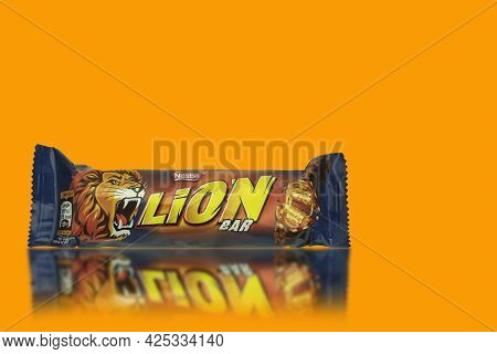Poland, Warsaw - June 24, 2021: Lion Chocolate Bar On A Yellow Background. Yellow Background With Co