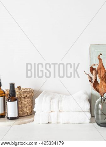 White Bath Background Front View With Glass Vase, Cosmetics, White Towels And Decor On White Shelf A