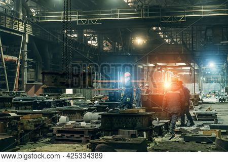 Workers On Production Line With Molds For Metal Cast In Industrial Metallurgy Workshop. Heavy Indust