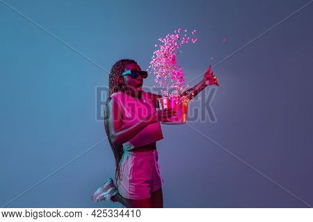 Watching Cinema. Young African Womans Portrait On Blue Studio Background In Neon Light. Concept Of Y
