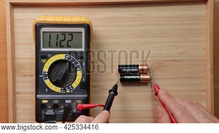 Budapest, Hungary - Circa 2021: Testing AA battery cells from Duracell with digital multimeter tool, voltage check showing low value, battery is used and discharged