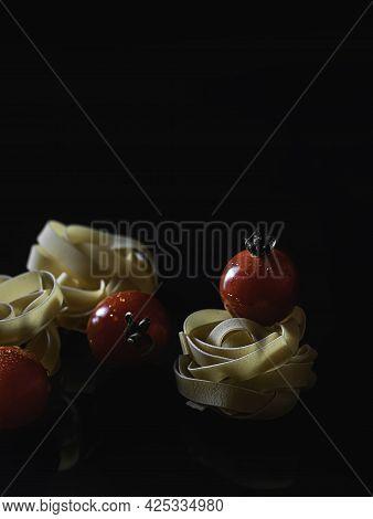 Uncooked Italian Pasta Fettuccine Nest On Black Background. Homemade Pasta. Italian Cuisine. Egg Noo