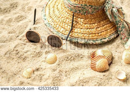 Straw Hat And Sunglasses Left On The Sand On The Beach Among Seashells
