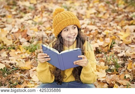 Knowledge Is Seed That Grows When You Read. Happy Kid Read Book Sitting On Autumn Leaves. Knowledge
