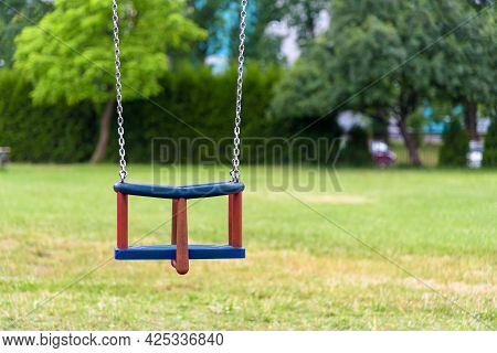 Empty Swing With Chains On The Playground