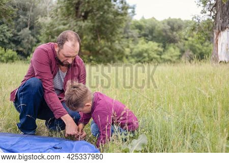 Father Is Teaching His Son To Pitch A Tent