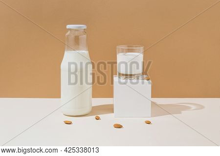 Glass With Vegan Milk From Almond Nuts With A Bottle On White Wooden Tray With Sunlit Background. Da