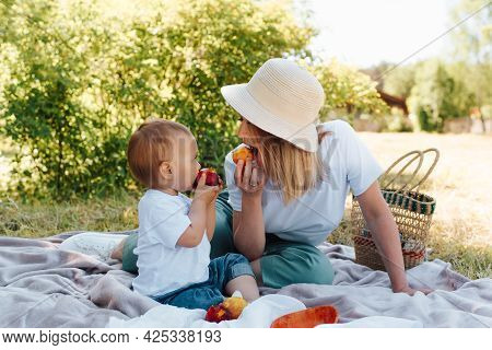 Family Picnic, Mom And Baby Eat Fruit Together, Outdoors. Young Mother In A Hat And Little Son Are R