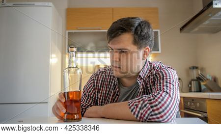 Young Woman Taking Bottle Of Alcohol During Conflict With Drunk Husband On Kitchen. Alcoholism And A