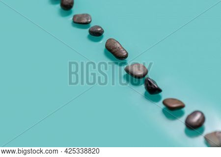 Small Stones, Similar To Pebbles, Lie Diagonally On A Turquoise Background. Horizontal Picture With