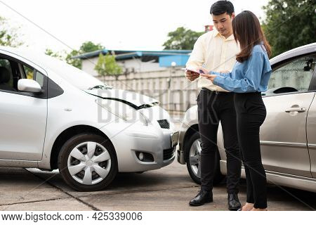 Asian Women Driver Talk To Insurance Agent For Examining Damaged Car And Customer Checking On Report