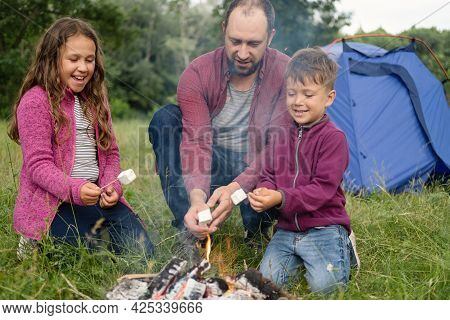 Happy Father, Daugther And Son Roasting Marshmallow At Campfire In Forest