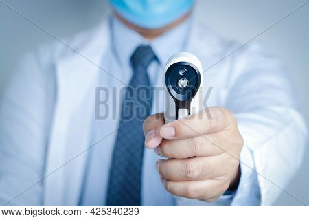 Doctors Wear A Mask And Gloves, Hold A Digital Thermometer To Examine The Patient. Healthcare Servic