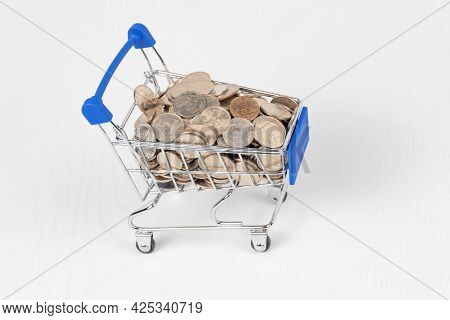 Metal Chrome Shiny Shopping Trolley On Wheels With Nickel Plated Coins Isolated On White Background.