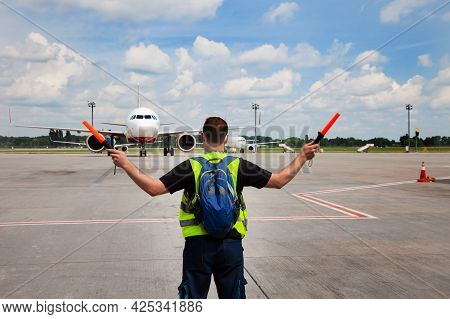 The Traffic Controller At The Airport Shows The Semaphore With Sticks To The Pilot Of The Plane Wher