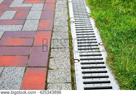 Grating Of The Drainage System For Drainage Of Rainwater In The Park At The Edge Of The Sidewalk Fro