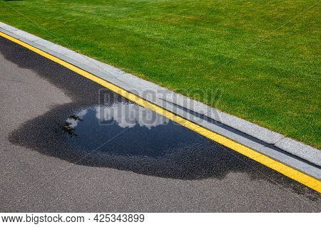 Puddle On Asphalt Road With Stormwater On The Side Of The Road With A Ditch For Water And A Glade Of