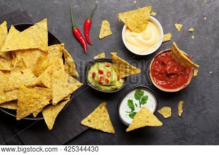 Mexican nachos chips with various sauces - guacamole, salsa, cheese and sour cream. Top view flat lay on stone table