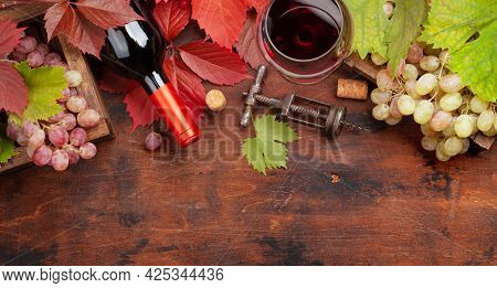 Red wine, autumn leaves and grapes on wooden table. Top view flat lay with copy space