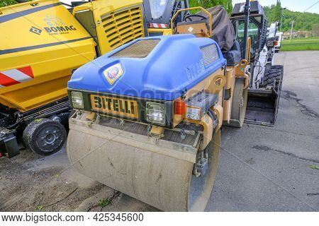June 2021 Parma, Italy: Blue Asphalt Paver Road Machine Bitelli Parked Across Other Heavy Industrial