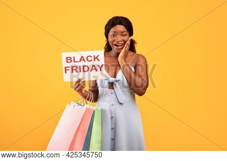 Excited Black Woman Holding Shopping Bags And Black Friday Sign, Touching Her Face In Disbelief On O