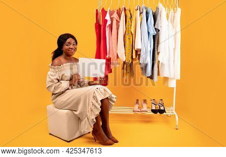 Full Length Of Pretty Black Woman Sitting With Empty Sign Near Clothing Rack Over Orange Studio Back